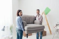 夫妇移动的家具在他们的新房里 免版税库存照片