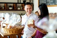 年轻夫妇购物的幸福在面包店商店 免版税图库摄影