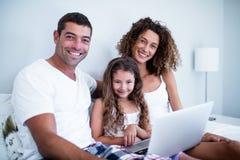 夫妇画象使用膝上型计算机的有他们的在床上的女儿的 免版税库存照片