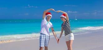 年轻夫妇画象在圣诞老人帽子的享用海滩 库存图片