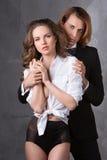 年轻夫妇画象在摆在演播室的爱的在经典衣裳穿戴了 免版税库存照片