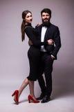 年轻夫妇画象在爱摆在的在灰色backround的经典衣裳穿戴了 有胡子的人在衣服,黑礼服的妇女 库存图片