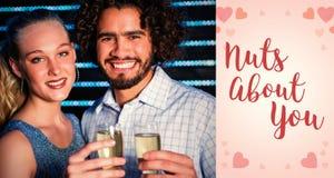 夫妇画象的综合图象拿着杯在酒吧的香槟的  免版税库存照片