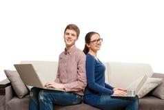 夫妇画象紧接坐有膝上型计算机的长沙发 库存照片