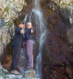 年轻夫妇临近在山的瀑布,丙氨酸Archa, Kyrgyzs 免版税库存照片