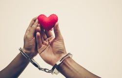 夫妇`递举行作为红色心脏与手袖口一起 库存照片