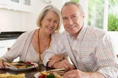 夫妇年长享用的膳食进餐时间一起 免版税库存图片