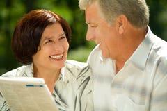 夫妇年长愉快的读取 免版税图库摄影