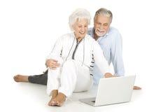 夫妇年长膝上型计算机使用 库存照片