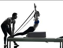 夫妇pilates改革者行使健身被隔绝 免版税库存照片