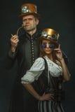 夫妇steampunk 有一个管子和一个女孩的一个人戴眼镜 免版税库存照片