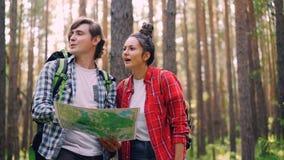 失去的游人在看地图,谈话和打手势然后发现方式和走对目的地的森林里站立 影视素材