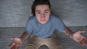 失望的一个少年坐一个灰色沙发的一个英俊的男孩 库存照片