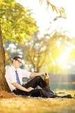 失望的人坐与瓶的一棵草在太阳的公园 免版税库存图片