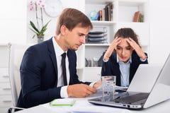 年轻失望的男人和妇女工友在牢固的办公室 免版税库存照片