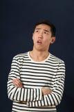 失望的年轻亚裔人用查寻横渡的手 免版税库存图片