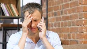 失望,不快乐,哀伤的人谈话在手机在创造性的工作地方 免版税库存照片