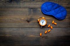 失眠概念 设法休眠 帮助得到睡觉 安眠药近的睡觉面具和闹钟在黑暗 免版税库存图片