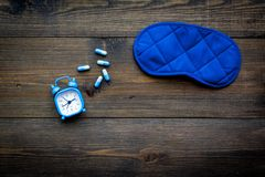 失眠概念 设法休眠 帮助得到睡觉 安眠药近的睡觉面具和闹钟在黑暗 免版税库存照片