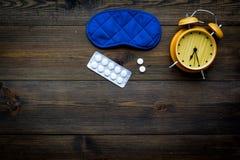 失眠概念 设法休眠 帮助得到睡觉 安眠药近的睡觉面具和闹钟在黑暗 图库摄影