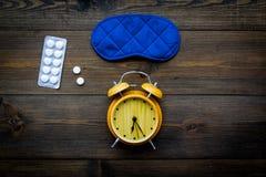 失眠概念 设法休眠 帮助得到睡觉 安眠药近的睡觉面具和闹钟在黑暗 库存照片