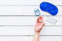 失眠概念 设法休眠 帮助得到睡觉 安眠药近的睡觉面具和闹钟  库存图片