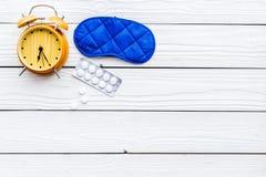 失眠概念 设法休眠 帮助得到睡觉 安眠药近的睡觉面具和闹钟  免版税库存图片