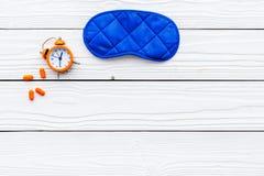 失眠概念 设法休眠 帮助得到睡觉 安眠药近的睡觉面具和闹钟  免版税库存照片