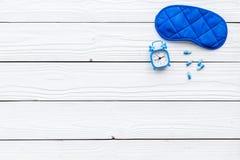 失眠概念 设法休眠 帮助得到睡觉 安眠药近的睡觉面具和闹钟  免版税图库摄影
