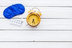 失眠概念 设法休眠 帮助得到睡觉 安眠药近的睡觉面具和闹钟  库存照片