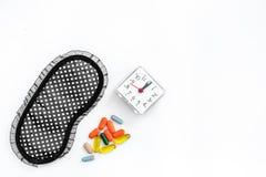 失眠近的睡眠面具和闹钟的安眠药在白色背景顶视图copyspace 库存照片