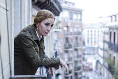 失去和哀伤的看起来妇女在家阳台遭受的消沉周道和孤零零 免版税库存照片