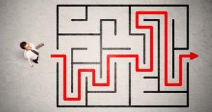失去的商人发现了在迷宫的方式有红色箭头的 图库摄影