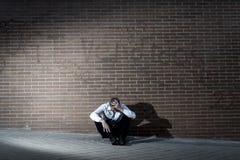 失去的工作在消沉丢失坐城市街角的商人 免版税库存照片