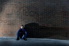 失去的工作在消沉失去坐地面街角的年轻绝望人 免版税图库摄影