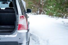 失败的汽车 与一根开放树干的背面图,冬天在森林里 免版税图库摄影