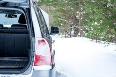 失败的汽车 与一根开放树干的背面图,冬天在森林里 免版税库存图片