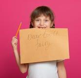 失去的牙女孩画象,在桃红色背景的演播室射击 免版税图库摄影