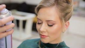 头发大师喷洒油漆,做卷毛,金发碧眼的女人,发廊 股票录像