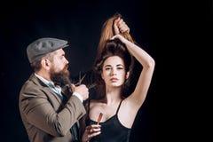 头发演播室 得到理发的秀丽妇女由美发师在理发店hairstudios 免版税图库摄影