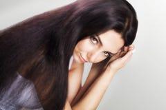 头发秀丽 方式 接触她长和健康棕色头发的妇女的一个模型 秀丽浅黑肤色的男人 在灰色bac隔绝的女孩 库存照片