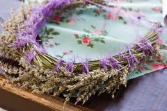 头发装饰品 干淡紫色一个精美花圈在一张蓝色桌上的 库存图片