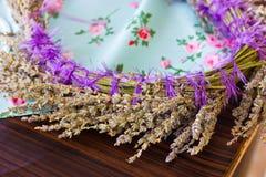头发装饰品 干淡紫色一个精美花圈在一张蓝色桌上的 免版税库存照片