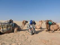 头巾的妇女,面孔是闭合的,与一头骆驼在撒哈拉大沙漠 库存照片