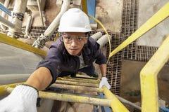 头戴安全帽的亚裔男性雇员爬梯子 免版税库存照片