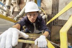 头戴安全帽的亚裔男性雇员爬梯子 免版税库存图片