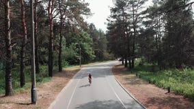 头戴桃红色成套装备和黑盔甲的女性逗人喜爱的骑自行车者骑一辆自行车在公园作为她的训练惯例的部分 循环的co 股票视频