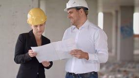 头戴防护盔甲的两位建筑师在建筑工地工作 免版税图库摄影