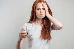 头疼 有看照相机的温度计的病的妇女 流感 流感 免版税库存照片