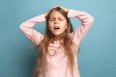 头疼 蓝色背景的青少年的女孩 表情和人情感概念 免版税库存照片